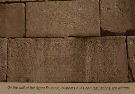 The wall in the agora fountain which is written the rules and regulations.